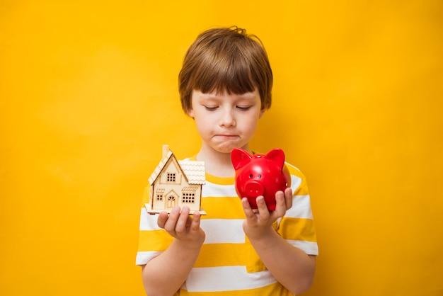 어린 시절의 꿈. 어린 소년은 꿈의 집과 돼지 저금통을 보유하고 있습니다. 행복한 삶, 집 또는 모기지 투자 개념
