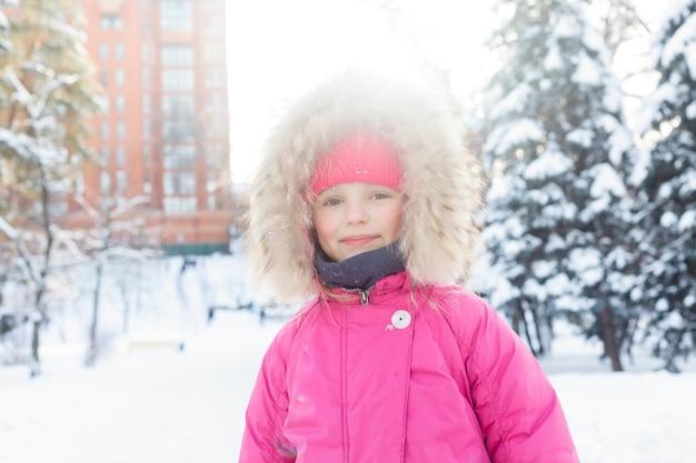 子供時代、ファッション、季節、人々のコンセプト – 冬の雪で遊ぶ4kの小さな女の子、雪だるまを作る幸せな子、雪だるまパー、クリスマス休暇の子供たち。冬服を着た幸せな女の子の顔