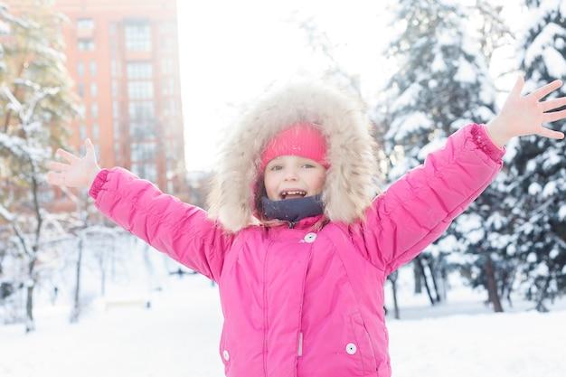 子供の頃、ファッション、季節、人々のコンセプト-雪の冬に遊ぶ4kの小さな女の子、雪だるまを作る幸せな子供、雪だるまパー、クリスマス休暇の子供たちを表示します。冬の服で幸せな女の子の顔