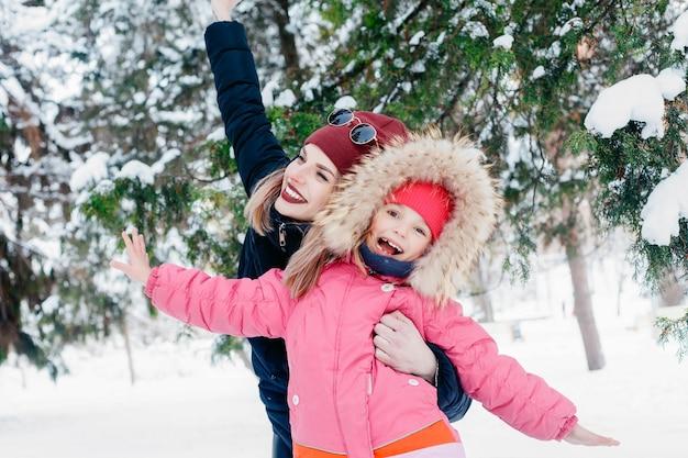 어린 시절, 패션, 계절, 그리고 사람들의 개념 - 눈을 날리는 그녀의 어머니를 바라보는 귀여운 소녀. 추운 화창한 날씨에 아침에 야외에서 겨울 산책하는 동안 행복한 가족.
