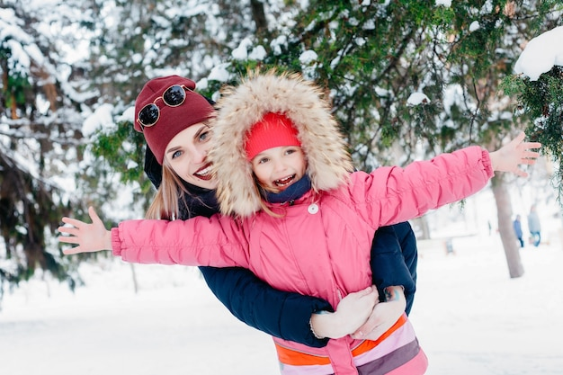 Childhood, fashion, season and people concept - cute little girl looking on her mother that is blowing away the snow. happy family during winter walk outdoors in the morning in cold sunny weather.