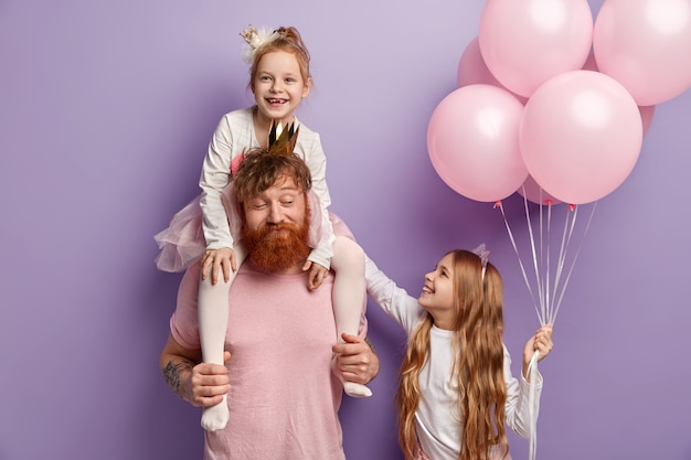 Childhood and fatherhood concept. red haired dad rides piggyback for little daughter, entertains children on birthday party. small child gives air balloons for friend, feel happiness, isolated