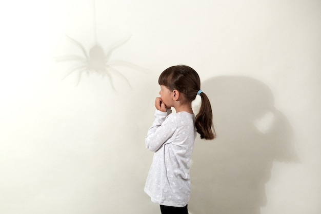Childhood fears. side view of small dark haired girl wearing white casual shirt having fear of insects, looking at shadow of spider on wall and biting fingernails, isolated over gray wall.