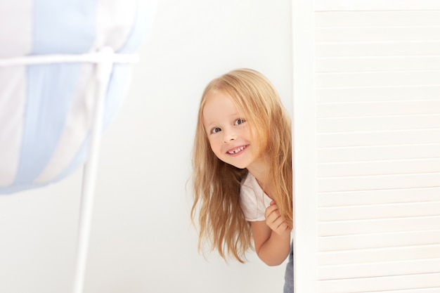 子供の頃、楽しさと人々のコンセプト-部屋のドアの後ろに隠れて幸せな笑みを浮かべて美しい少女。子供は家でかくれんぼをします。ポジティブベイビー。女の子はドアの後ろから覗いていて驚いています