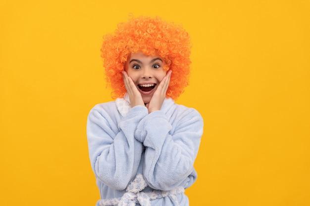 子供の幸せ。誕生日やパジャマパーティー。巻き毛のピエロのかつらで面白い子供。派手な子供は家庭用バスローブを着ます。居心地の良いパジャマでオレンジ色の髪の10代の少女を驚かせた。おはよう。