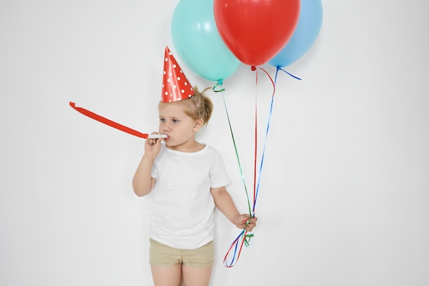 Infanzia, felicità, celebrazione e concetto di divertimento. carino adorabile piccolo bambino che soffia fischietto, con palloncini colorati, sentirsi felice, festeggiare il compleanno, in posa al muro bianco