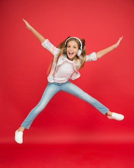 어린 시절의 행복. 행복한 아이는 음악을 듣습니다. 자유와 성공. 이어폰에 어린 소녀입니다. 그녀의 꿈에 도달하십시오. 공중에 날다. 미쳐간다. 흥분된 작은 소녀는 헤드셋을 착용합니다. 좋아하는 노래와 함께 춤을 춥니다.