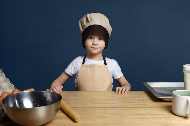子供の頃、趣味、食べ物、栄養、料理、ベーキング、ベーカリーのコンセプト。キッチンでペストリーを作るシェフの制服を着た興奮したハンサムな青い目をした白人の小さな男の子の孤立したショット、コピースペース