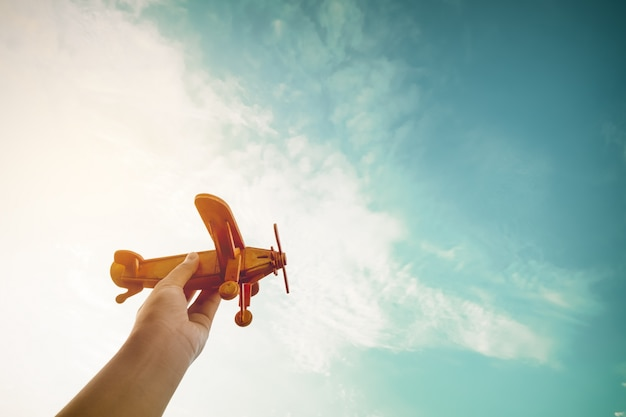 어린 시절 영감-장난감 비행기를 들고 꿈을 꾸는 어린이의 손에 파일럿이되고 싶어-빈티지 필터 효과 프리미엄 사진