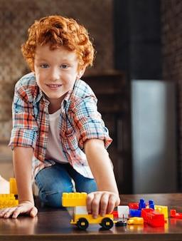 어린 시절은 재미에 관한 것입니다. 나무 테이블에 앉아 재생하는 동안 카메라에 포즈 스마트 빨간 머리 아이