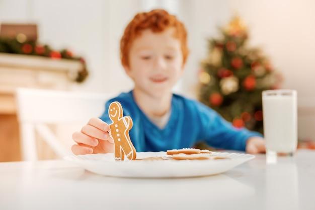 Детство - лучшее время. селективный акцент на вкусный домашний пряничный человечек, которого держит улыбающийся ребенок, сидящий за столом и играющий дома.