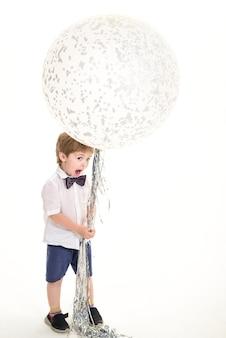 大きな風船パーティー気分のお祝いのコンセプトを持つ子供時代の子供大きな白い風船面白い男の子と遊ぶ