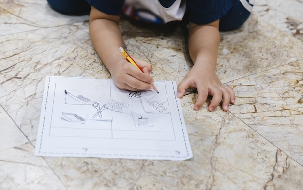 Childhood learning to use a pencil to draw and write on paper.