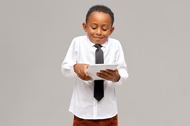 Childhood, modern technology and addiction. cute afro american schoolboy addicted to electronic gadgets using digital tablet to play video games, having absorbed facial expression