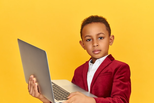 Childhood, modern technology and electronic gadgets concept. serious handsome schoolboy in stylish clothes holding open generic laptop with confident look, surfing internet while doing homework