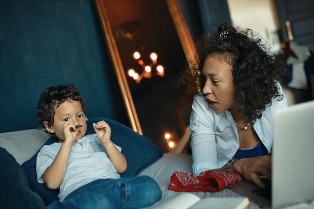 子供の頃、子育て、ホームスクーリング、オンライン教育の概念。彼女の愛らしい就学前の子供に数字を教えながらラップトップを使用して若い混血の母親