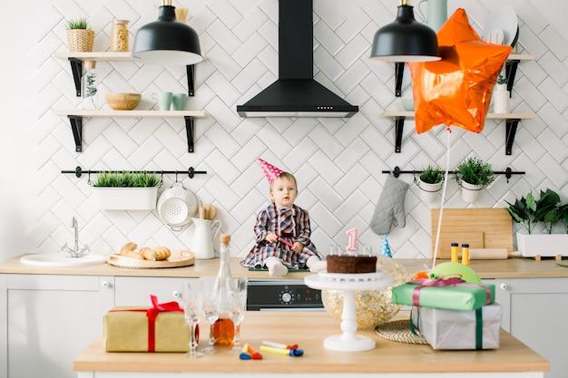 Концепция детства, людей и торжества - счастливый ребёнок в розовой шляпе дня рождения сидя в кухне на вечеринке по случаю дня рождения дома. стол с праздничным тортом, подарками, воздушными шариками и рогами для вечеринок