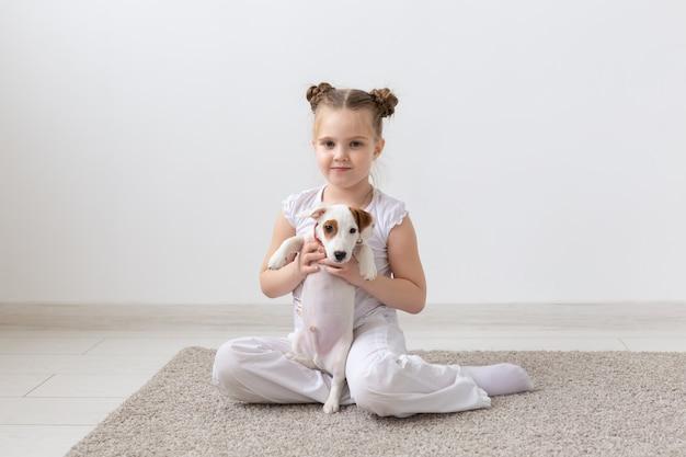 子供の頃、ペットと犬のコンセプト-子犬と一緒に床にポーズをとる小さな子供の女の子。