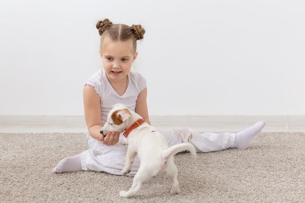 Концепция детства, домашних животных и собак - маленькая девочка щенка и ребенка в белой рубашке с удовольствием.
