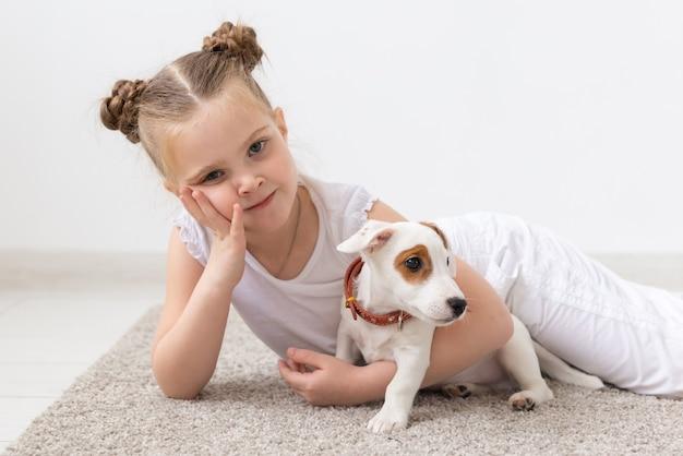 子供の頃のペットと犬のコンセプトは、子犬と一緒に床にポーズをとる小さな子供の女の子をタイトルしました