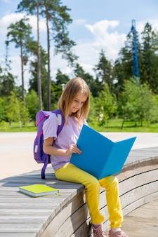 어린 시절 학교 및 교육 개념 집중된 중학교 소녀는 공공 공원에서 책을 읽습니다