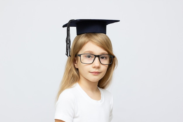 Childhood, school, education, learning and people concept - happy girl with glasses in bachelor hat or mortarboard over white background