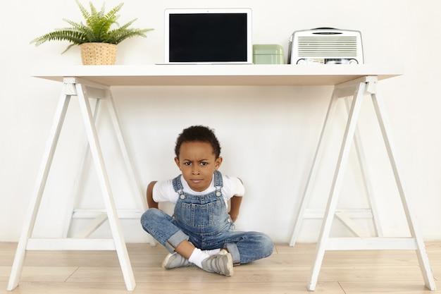 Childhood and upbringing concept. indoor image of moody grumpy stubborn little dark skinned boy in sneakers