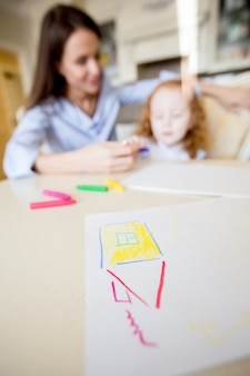 Childish drawing of house on table and family