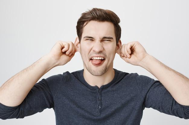 Uomo divertente infantile che tira le orecchie e mostra la lingua, facendo smorfie