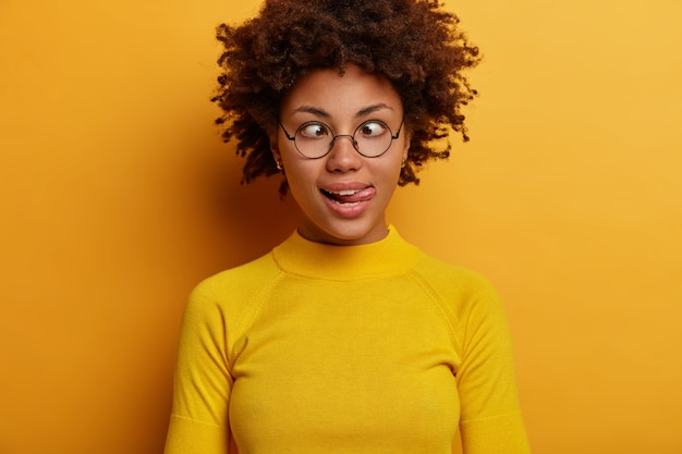 Childish funny woman with afro hair sticks out tongue, crosses eyes, goes crazy and mad, makes grimace, wears round spectacles and casual jumper, poses against yellow wall, has playful mood