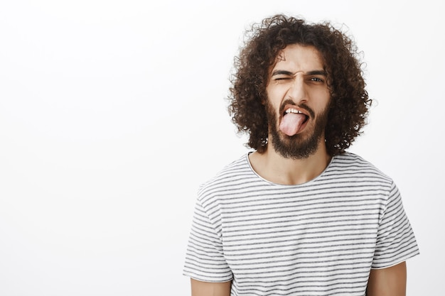 Childish good-looking eastern guy with beard and curly hair, showing tongue and winking playfully, feeling carefree and living relaxed way of life