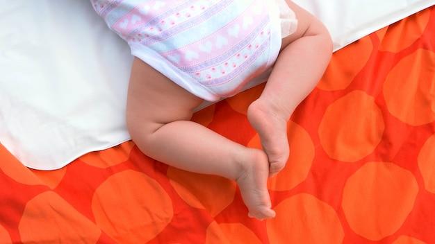 Детские ножки на одеяле. младенческая девочка, лежа на животе. новая концепция семьи и воспитания.