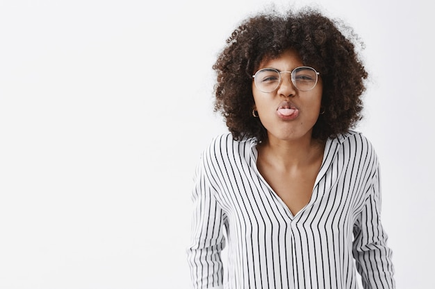 Childish and playful funny african american adult woman with afro hairstyle in striped office blouse and glasses bending towards and showing tongue wrinkling nose joyfully