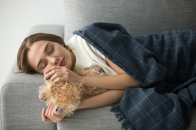 ぬいぐるみが付いている柔らかい快適なソファで寝ている幼稚な女性