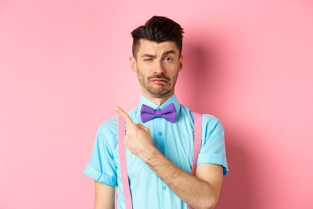 ピンクの背景の上に立って、指の左上隅を指して、何かに不平を言っている間、悲しくて偽の泣き声を振るう幼稚な若い男。