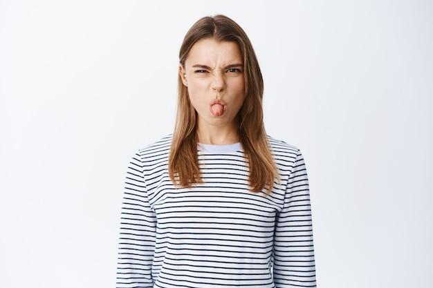 幼稚な若い女性は、不快な行動をし、舌を見せ、怒って眉をひそめ、嫌悪と軽蔑を表現し、不機嫌になり、白い壁の上に立っています。
