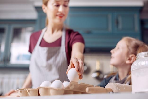子供のような好奇心。カートンから卵を取り出し、たくさんの質問をしている娘とおしゃべりしながら生地を作る快適な若い女性の手に焦点が当てられています
