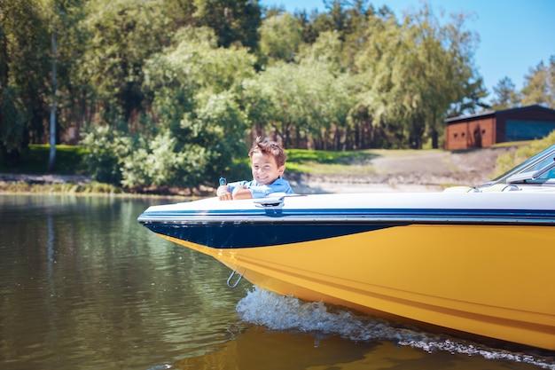 子供のような好奇心。モーターボートの船首でリラックスし、カメラに向かって明るく笑いながら景色を楽しんでいる明るい男の子