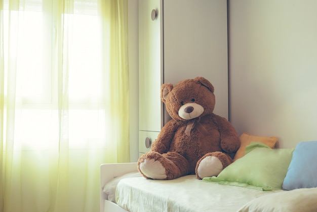 Childrem room with a brown teddy bear on the bed