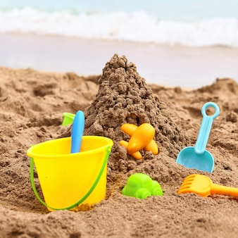子供のビーチおもちゃ-晴れた日に砂の上にバケツ、スペード、シャベル