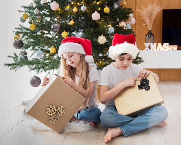 Дети - мальчик и девочка играют возле елки. интерьер гостиной с елкой и украшениями. новый год. дарение подарков.