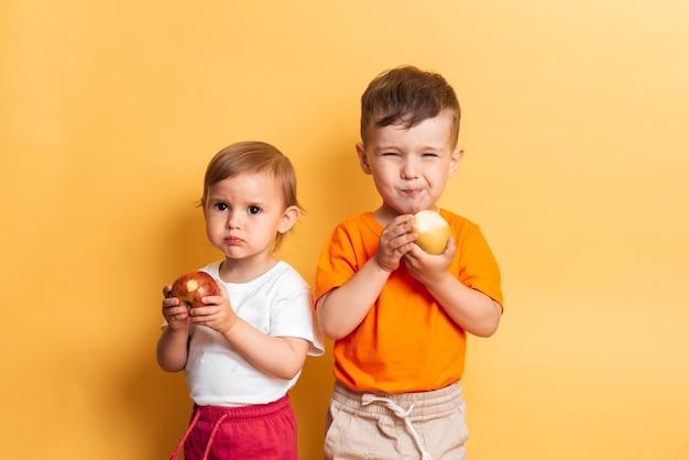 男の子と女の子の子供たちは新鮮なリンゴを食べます。黄色の背景に兄と妹。健康食品とビタミン