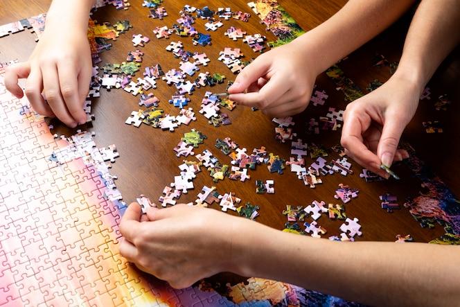 i bambini e le mani degli adulti impilano un puzzle di colore su una tavola di legno