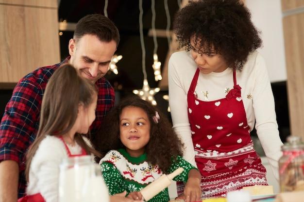 子供たちは両親がクッキーを作るのを手伝います