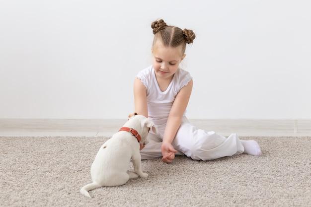 子供と動物の概念-床に座っているパジャマを着た子供の女の子と子犬。