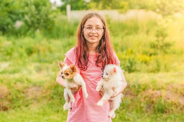 Концепция детей и животных. девочка и две собаки чихуахуа и шпиц. девушка с двумя собаками. подросток