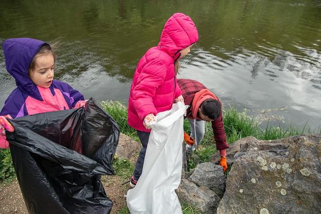 Дети и папа убирают мусор в лесу у реки.