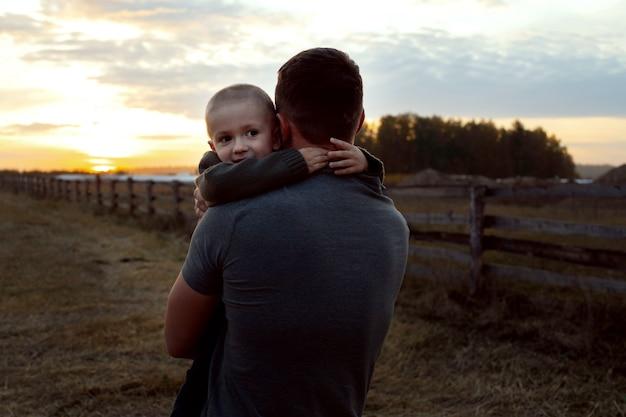 Дети и отец гуляют на закате в скошенном поле
