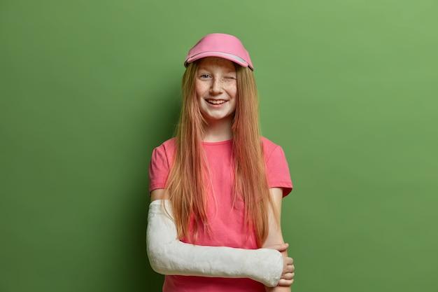 어린이 및 건강 관리 개념. 쾌활한 빨간 머리 소녀는 캐스트에서 부러진 팔로 포즈를 취하고, 추락하거나 도로에서 사고를당한 후 부상을 입었고, 여름 티셔츠와 모자를 입고 눈을 윙크하고 외상을 잊어 버렸습니다.