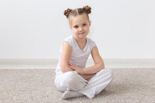 子供と子供のコンセプト-思いやりのある顔で床に座っている白いシャツを着た小さな子供の女の子。